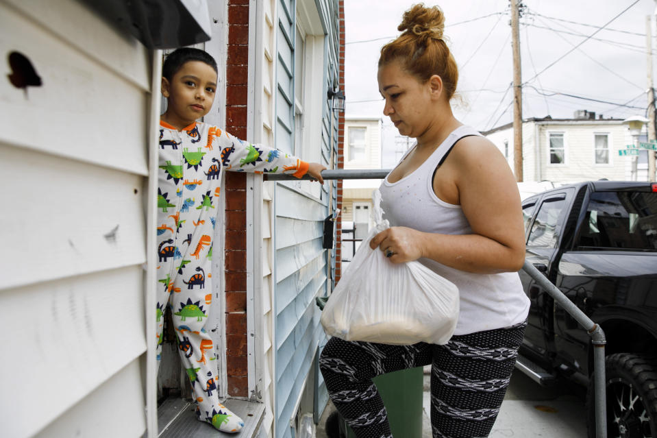 FILE - In this April 14, 2020, file photo, Roberto, 5, stands in their doorway in his pajama's as his mother Arely Martinez carries in a bag of food in Baltimore. As the coronavirus spreads deeper across America, it is ravaging through the homes and communities of Latinos. Martinez delayed medical help for two weeks after getting a fever and headache, struggling to breathe and losing her sense of smell. Lack of insurance, her undocumented status and misinformation about the pandemic kept the Honduran native who now lives in Baltimore home, but she ultimately went to the hospital. (AP Photo/Jacquelyn Martin, File)