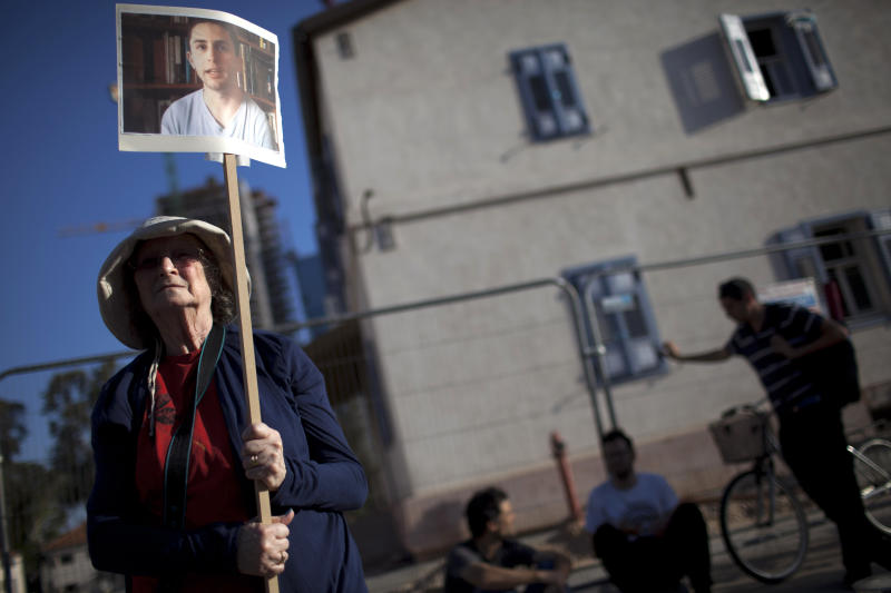 A left wing activist holds a picture of Israeli conscientious objector Natan Blanc during a protest calling for his release from military prison, in front of the ministry of defense office in Tel Aviv, Tuesday, May 21, 2013. The Israeli military has jailed Blanc for six months because of his opposition to Israel's occupation of the West Bank, in one of the most protracted cases by a conscientious objector in years. The refusal by 20-year-old Natan Blanc to serve in the military has shined a light on Israeli policies toward the Palestinians. It has also put the military in a delicate position as it tries to resolve the case, since releasing him could set an unwanted precedent while keeping him jailed could turn into a public relations debacle. (AP Photo/Oded Balilty)