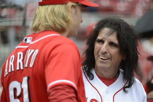 Rock and Roll Hall-of-Famer Alice Cooper, right, talks with Cincinnati Reds pitcher Bronson Arroyo before throwing out the ceremonial first pitch before a baseball game between the Reds and the Seattle Mariners at Great American Ball Park in Cincinnati, Saturday, July 6, 2013. (AP Photo/Michael E. Keating)