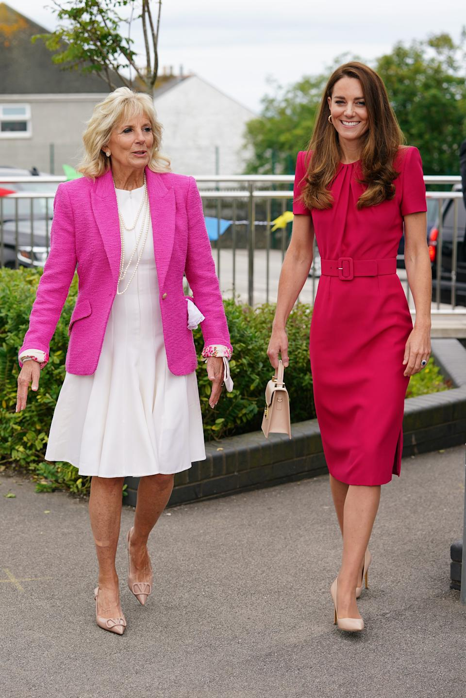The Duchess of Cambridge (R) and U.S. First Lady Dr Jill Biden (L) wowed in vibrant shades of pink on an official engagement in Cornwall. (Photo by Aaron Chown/WPA Pool/Getty Images)