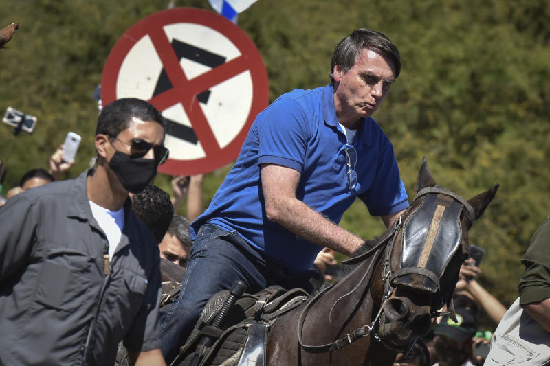 Brazil's President Jair Bolsonaro rides a horse greeting supporters outside the presidential palace in Brasilia, Brazil, Sunday, May 31, 2020. Bolsonaro mounted a horse from police that were guarding supporters of his government gathered outside the Planalto Palace. (AP Photo/Andre Borges)