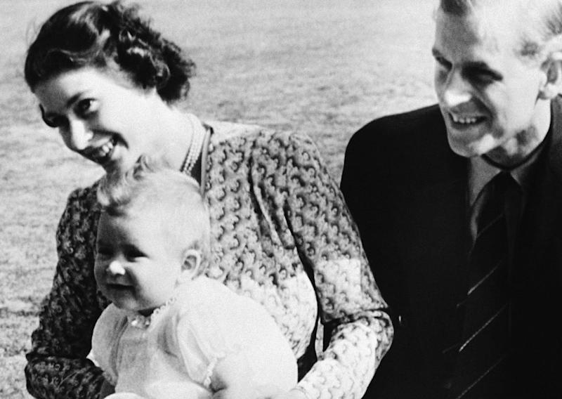 FILE - In this July 18, 1949 file photo, Prince Charles, foreground left, the eight-month-old son of Princess Elizabeth of England, left, and his father Philip, poses for a photo, on the Windlesham Moor, their summer residence, in Ascot, England. Prince Charles is readying the paperwork to claim his pension when he turns 65 Thursday, Nov. 14, 2013, but he still hasn't started the job he was born to do. (AP Photo, File)