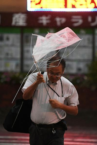 This umbrella provided little shelter for a man crossing a street in Tokyo during Typhoon Faxai