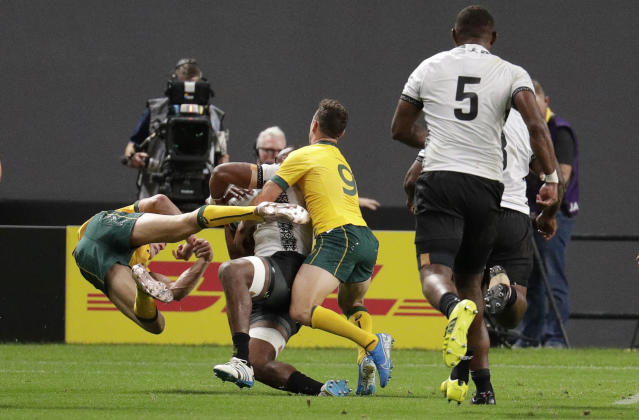 Australia's Reece Hodge, left, flies as he is pushed away by Fiji's Peceli Yato during the Rugby World Cup Pool D game at Sapporo Dome between Australia and Fiji in Sapporo, Japan, Saturday, Sept. 21, 2019. (AP Photo/Aaron Favila)