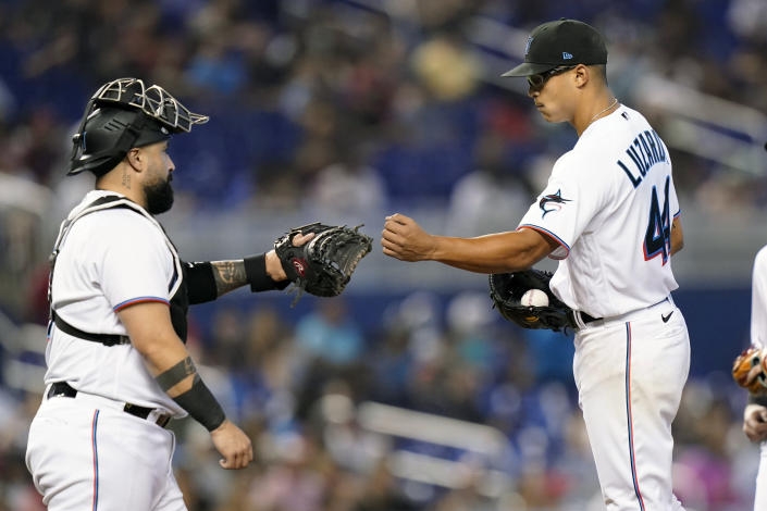 Miami Marlins starting pitcher Jesus Luzardo, right, bumps fists with catcher Sandy Leon as he is relieved during the seventh inning of a baseball game against the Cincinnati Reds, Sunday, Aug. 29, 2021, in Miami. The Marlins won 2-1. (AP Photo/Lynne Sladky)