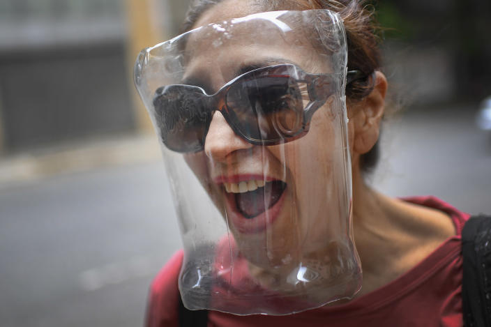 A woman wears a face shield made from a plastic bottle container, amid the spread of the new coronavirus in Caracas, Venezuela, Saturday, April 18, 2020. (AP Photo/Matias Delacroix)