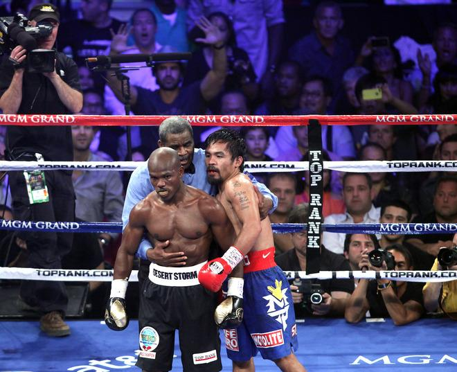 Timothy Bradley (L) of the US and Manny Pacquiao (R) of the Philippines are guided to their coners by by referee Robert Byrd  (C) during their WBO welterweight title match  at the MGM Grand Arena on June 9, 2012 in Las Vegas, Nevada.  Unbeaten Bradley ended Pacquiao's long unbeaten run with a controversial split decision victory over the Filipino ring icon.     AFP PHOTO /  John GurzinskiJOHN GURZINSKI/AFP/GettyImages