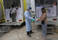 A health worker sprays disinfectant on hands after collecting a nasal swab from worker in a local entertainment venue area where a new cluster of COVID-19 infections were found in Bangkok, Thailand, Thursday, April 8, 2021. Thailand has confirmed its first local cases of the coronavirus variant first detected in the U.K., raising the likelihood that it is facing a new wave of the pandemic, a senior doctor said Wednesday. (AP Photo/Sakchai Lalit)