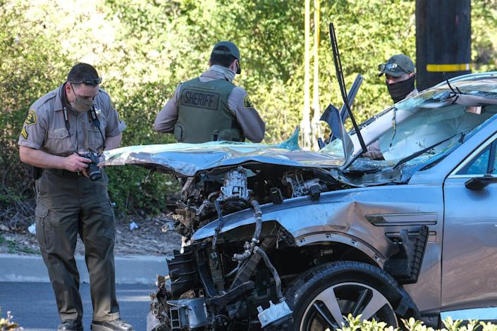 Law enforcement officers inspect the car driven by Tiger Woods.