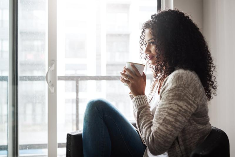 Shot of a cheerful young woman enjoying a cup of coffee while being seated on a chair at home during the day