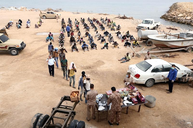 Migrants arrested earlier in the week receive food distribution in Tajura, a coastal suburb of the Libyan capital Tripoli on October 10, 2015 (AFP Photo/Mahmud Turkia)