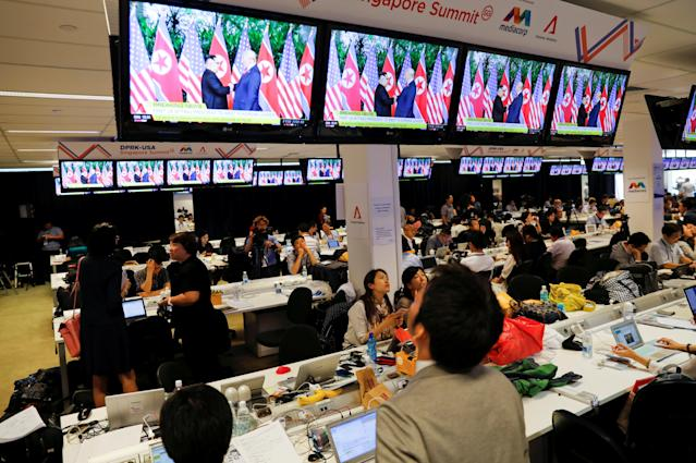 <p>News reports about the meeting between President Trump and North Korea's leader Kim Jong Un are viewed at a media center for the summit in Singapore. (Photo: Tyrone Siu/Reuters) </p>