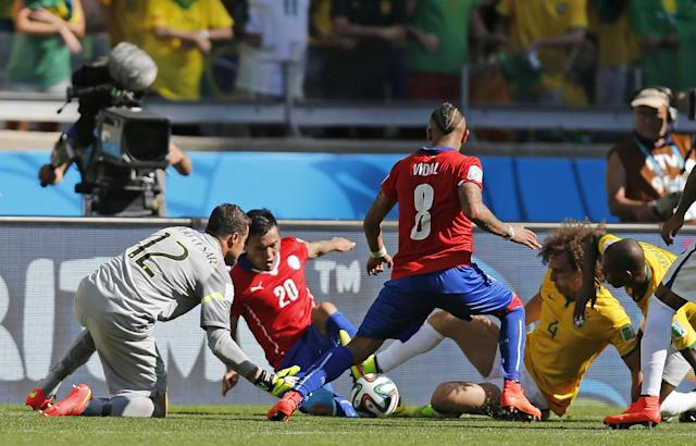 Brazil's goalkeeper Julio Cesar tries to grab the ball as Chile's Charles Aranguiz, second from left, and Chile's Arturo Vidal, center go for goal during the World Cup round of 16 soccer match between Brazil and Chile at the Mineirao Stadium in Belo Horizonte, Brazil, Saturday, June 28, 2014. Second from right is Brazil's David Luiz. (AP Photo/Frank Augstein)