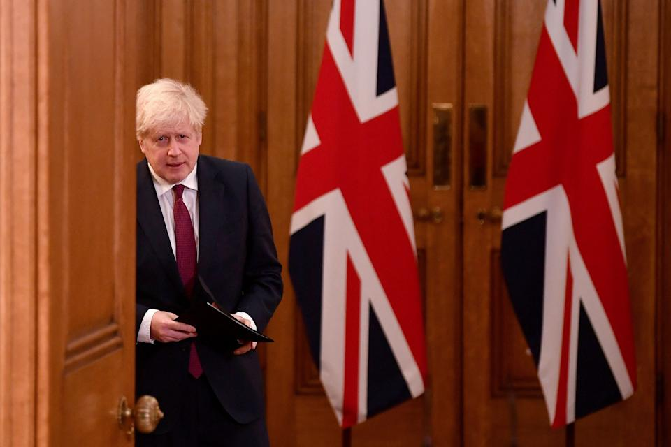 "Britain's Prime Minister Boris Johnson walks past union flags as he arrives to attend a virtual press conference inside 10 Downing Street in central London on December 19, 2020. - British Prime Minister Boris Johnson on Saturday announced a ""stay at home"" order for London and southeast England to slow a new coronavirus strain that is significantly more infectious. The new strain of the virus ""does appear to be passed on significantly more easily,"" Johnson said at a televised briefing. He ordered new restrictions for London and south-eastern England from Sunday, saying that under the new ""tier four"" rules, ""residents in those areas must stay at home"" at least until December 30. (Photo by TOBY MELVILLE / POOL / AFP) (Photo by TOBY MELVILLE/POOL/AFP via Getty Images)"