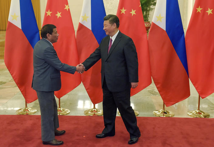 FILE - In this May 15, 2017, file photo, Philippine President Rodrigo Duterte, left, is greeted by Chinese President Xi Jinping prior to their bilateral meeting held on the sidelines of the Belt and Road Forum for International Cooperation at the Great Hall of the People in Beijing. (Etienne Oliveau/Pool Photo via AP, File)