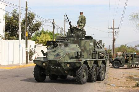 """A soldier atop a vehicle is seen outside the Forensic Medical Service (SEMEFO) after the arrival of the body of Francisco Zazueta, also known as """"Pancho Chimal,"""" in Culiacan, in Mexico's northern Sinaloa state April 15, 2017. REUTERS/Jesus Bustamante"""