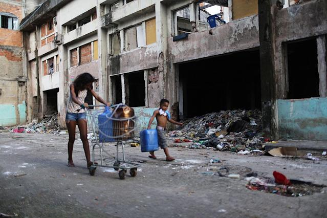 <p>Young residents haul water collected from hoses back to their family's home in the Mangueira favela, May 4, 2017, in Rio de Janeiro. (Photo: Mario Tama/Getty Images) </p>
