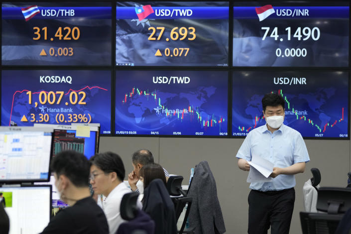 A currency trader passes by screens showing foreign exchange rates at the foreign exchange dealing room of the KEB Hana Bank headquarters in Seoul, South Korea, Friday, June 18, 2021. Asian shares mostly rose Friday, as investors digested the latest message from the U.S. Federal Reserve on raising short-term interest rates by late 2023. (AP Photo/Ahn Young-joon)