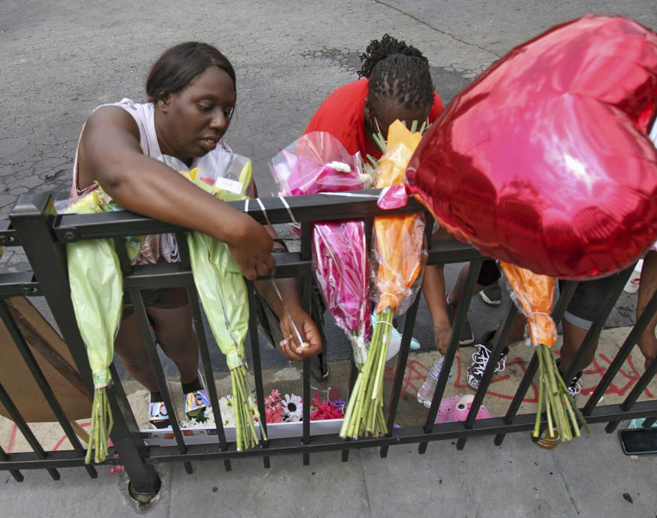 People attend to a memorial at the site of a destroyed Wendy's restaurant Sunday, June 14, 2020, in Atlanta. On Saturday, protestors set fire to the Wendy's where Rayshard Brooks, a black man, was shot and killed by Atlanta police Friday evening following a struggle in the drive-thru line. (Steve Schaefer/Atlanta Journal-Constitution via AP)