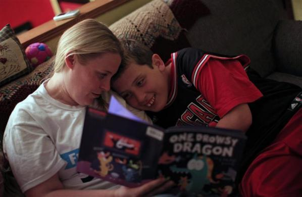 Holly Roos reads to her son Parker, who suffers from Fragile X, at their home in Canton, Illinois, April 4, 2012.