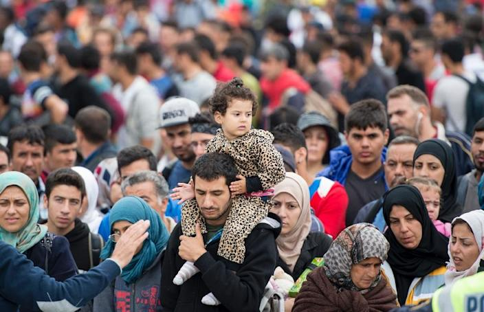 Migrants wait to board buses at the Austrian-Hungarian border to a train station in the Austrian village of Nickelsdorf, on September 5, 2015 (AFP Photo/Joe Klamar)