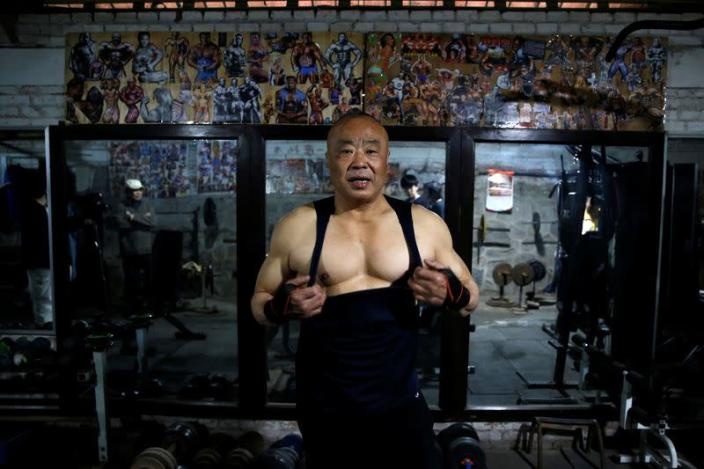 Xu Wei, a 63-year-old former factory worker and the current gym manager, show his muscles at the gym which has been turned from a bicycle shed inside a residential compound in the southwest of Beijing