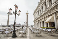 A waiter works in a restaurant in Venice, northern Italy, Saturday, May 1, 2021. Italy is gradually reopening after six months of rotating virus closures allowing outdoor dining. (Filippo Ciappi/LaPresse via AP)