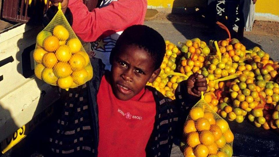 Unidentified children carry oranges from a pickup truck outside Nonqubela train station August 11, 2001 in Site B Khayelitsha, a township located approximately 21 miles outside Cape Town, South Africa.