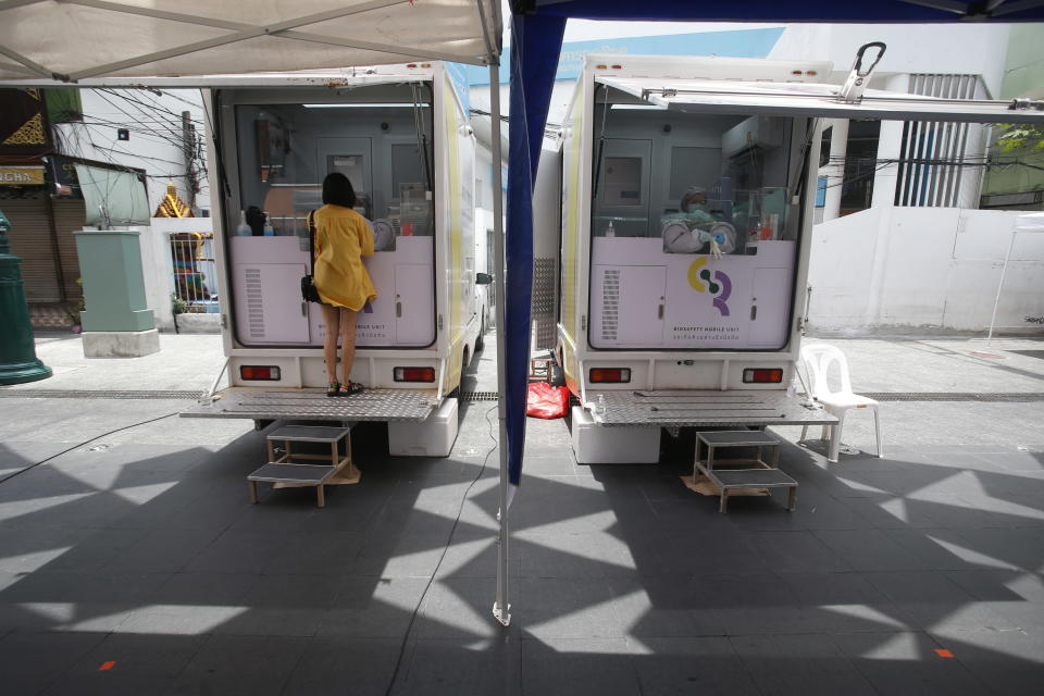 A woman waits for a COVID-19 swab test in front of one of the mobile testing units in Khaosan Road in Bangkok, Thailand Wednesday, April 14, 2021. Thailand recorded more than 1,000 COVID-19 infections on Wednesday, setting a daily record and adding pressure on the government to do more to control the country's spiking transmission rates. (AP Photo/Somchai Chanjirakitti)