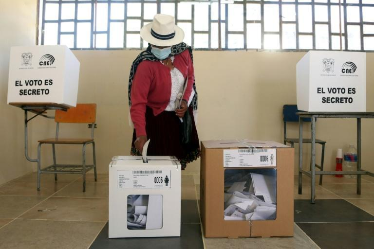 A woman casts her vote in Cuenca, Ecuador, during the general elections