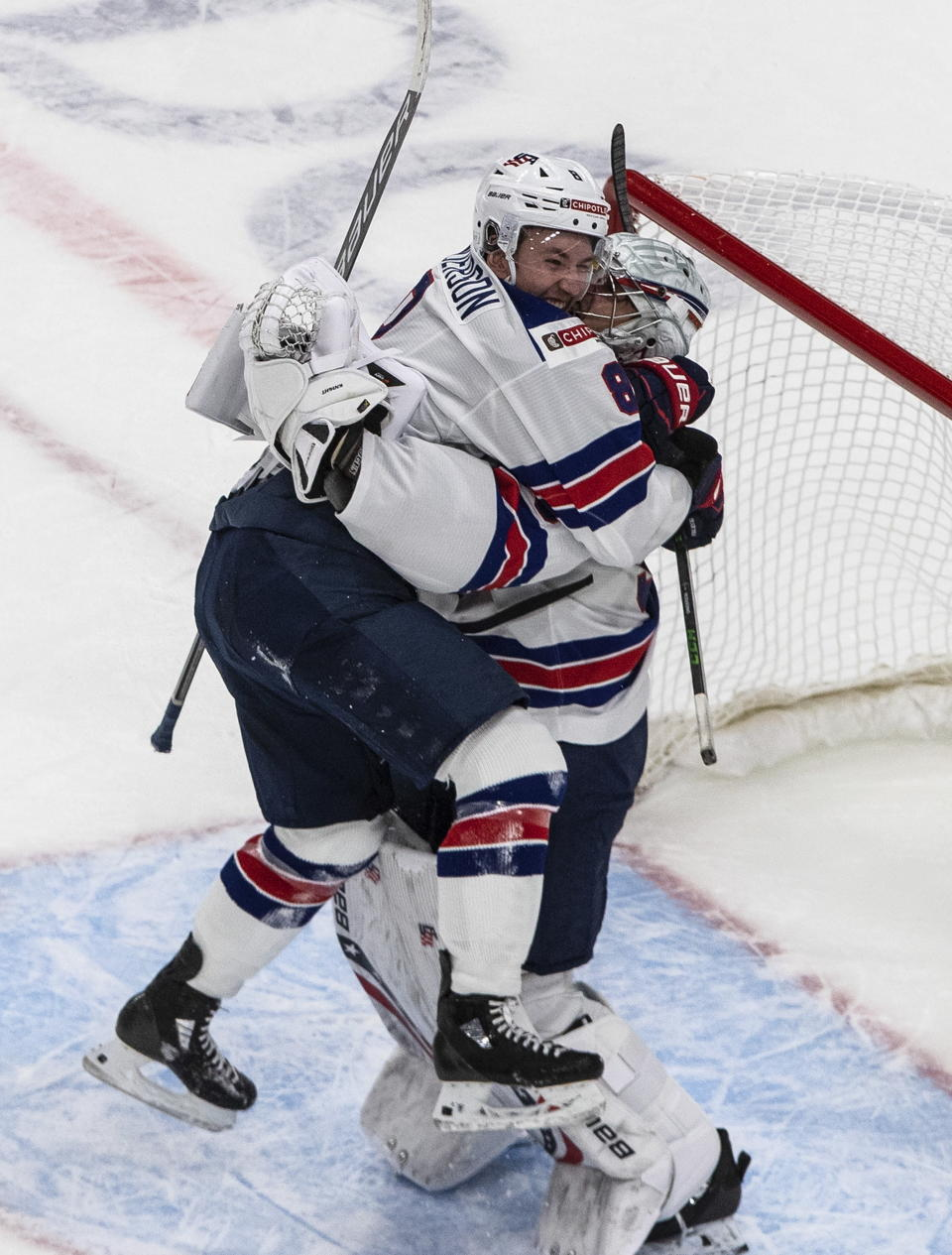 United States' Jake Sanderson (8) and Spencer Knight (30) celebrate the team's win over Canada in the championship game in the IIHF World Junior Hockey Championship, Tuesday, Jan. 5, 2021, in Edmonton, Alberta. (Jason Franson/The Canadian Press via AP)