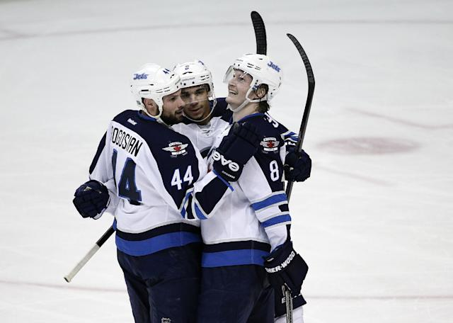 Winnipeg Jets' Evander Kane, center, celebrates his goal with Zach Bogosian, left, and Jacob Trouba during the second period of an NHL hockey game against the Anaheim Ducks, Tuesday, Jan. 21, 2014, in Anaheim, Calif. (AP Photo/Jae C. Hong)