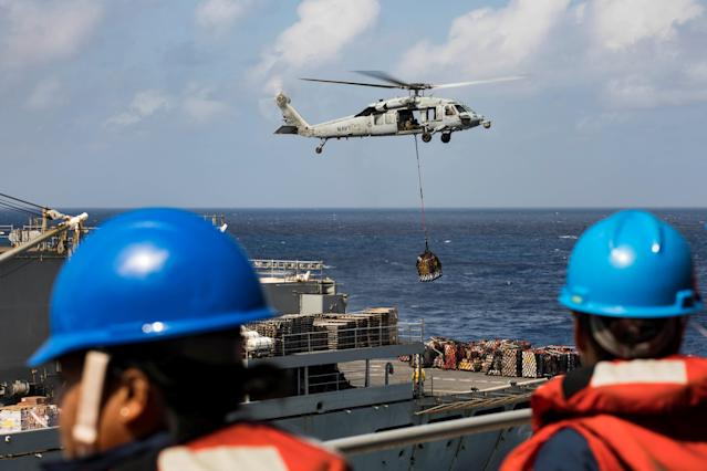 <p>Sailors aboard the amphibious assault ship USS Kearsarge (LHD 3) observe as an MH-60 Sea Hawk helicopter transfers pallets of supplies from the fast combat support ship USNS Supply (T-AOE 6) during replenishment-at-sea for continuing operations as part of Hurricane Maria relief efforts in Puerto Rico on Sept. 28, 2017. (Photo: Jacob A. Goff/U.S. Navy/Handout via Reuters) </p>