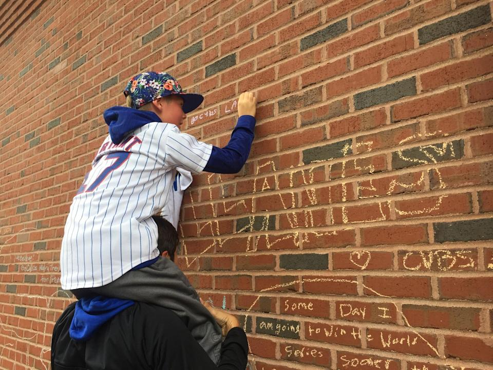 A young Cubs fan writes on the Wrigley brick wall. (Mike Oz / Yahoo Sports)