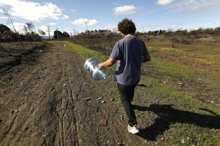 A person carries an empty water jug down a dirt path