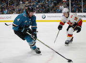 San Jose Sharks' Brenden Dillon (4) carries the puck against Calgary Flames' Matthew Tkachuk (19) in the first period of an NHL hockey game in San Jose, Calif., Sunday, Nov. 11, 2018. (AP Photo/Josie Lepe)