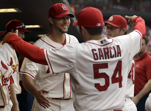 St. Louis Cardinals starting pitcher Adam Wainwright, left, gets a hug from teammate Jaime Garcia (54) as Shelby Miller, right, looks on after Wainwright was removed from a baseball game against the Chicago Cubs during the sixth inning on Saturday, Sept. 28, 2013, in St. Louis. (AP Photo/Jeff Roberson)