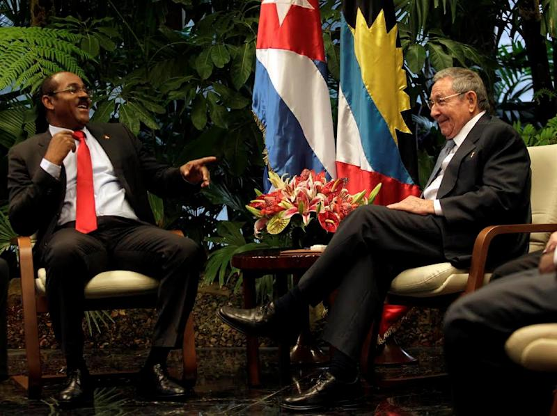 Antigua and Barbuda's Prime Minister Gaston Browne (R) is welcomed by Cuban President Raul Castro at the Revolution Palace in Havana, on December 7, 2014