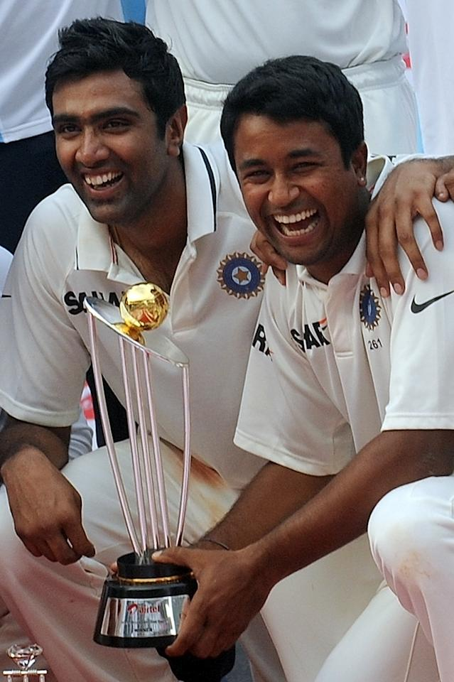 Indian bowlers Ravichandran Ashwin (L) and Pragyan Ojha pose with the trophy after India drew the third test cricket match between India and West Indies at the Wankhede stadium in Mumbai on November 26, 2011. India won the series 2-0. AFP PHOTO/ Punit PARANJPE