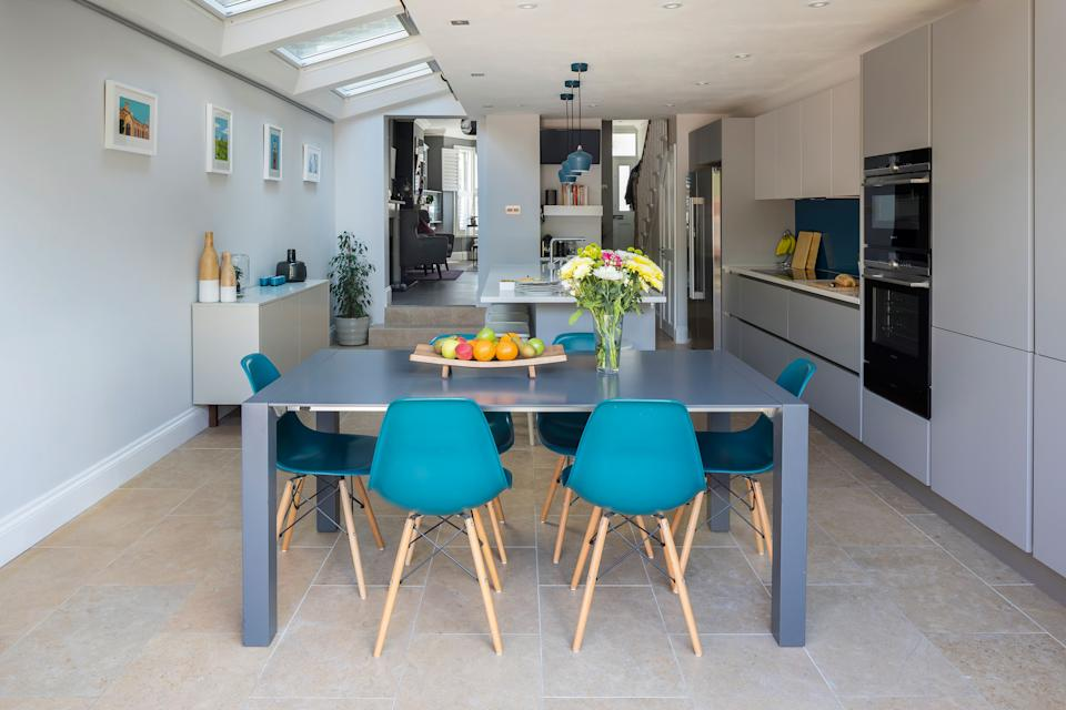 open plan modern kitchen diner with rooflights, blue dining chairs and glossy handleless cabinets