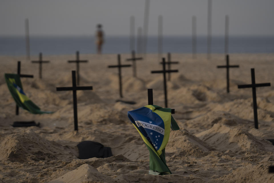 A Brazilian flag hangs on a cross marking a symbolic grave dug by activists from the NGO Rio de Paz to protest the government's handling of the COVID-19 pandemic, on Copacabana beach in Rio de Janeiro, Brazil, Thursday, June 11, 2020.A Brazilian Supreme Court justice ordered the government of President Jair Bolsonaro to resume publication of full COVID-19 data, including the cumulative death toll, following allegations the government was trying to hide the severity of the pandemic in Latin America's biggest country. (AP Photo/Leo Correa)