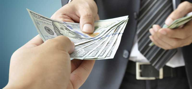 A businessman hands cash to an outstretched hand.