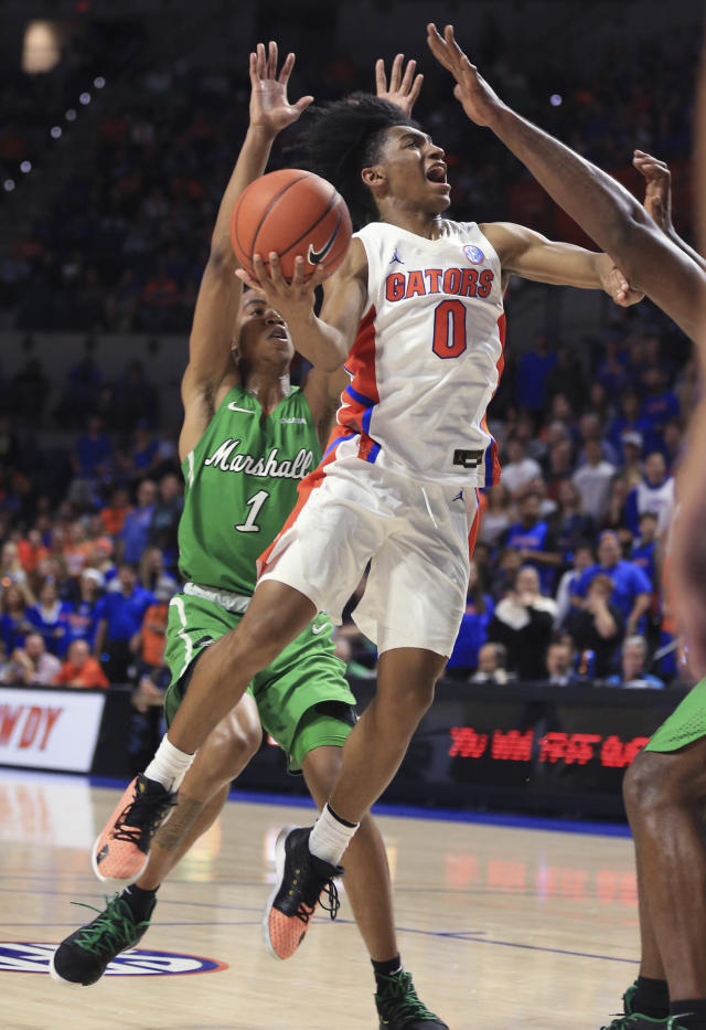 Florida guard Ques Glover (0) makes a layup past Marshall guard Taevion Kinsey (1) during the second half of an NCAA college basketball game Friday, Nov. 29, 2019, in Gainesville, Fla. (AP Photo/Matt Stamey)