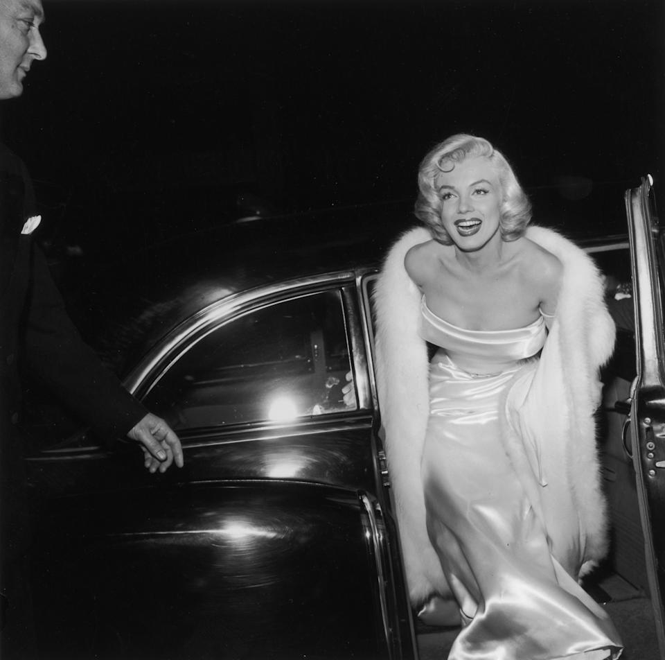 1954:  EXCLUSIVE American actor Marilyn Monroe (1926  - 1962) emerges from a car, wearing a strapless white gown and white fur coat at the premiere of director Walter Lang's film 'There's No Business Like Show Business'.  (Photo by M. Garrett/Murray Garrett/Getty Images)