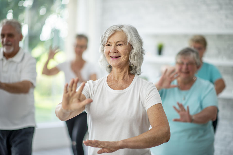 A group of seniors spend an afternoon indoors in a health center. They are doing group tai chi together.