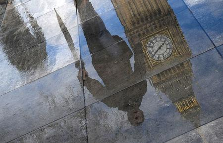 The Elizabeth Tower, commonly known as Big Ben, together with walkers are seen reflected in a puddle in London, Britain