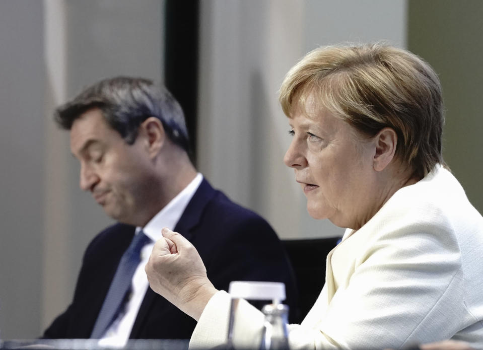 German Chancellor Angela Merkel, foreground and Markus Soder, Prime Minister of Bavaria and CSU Chairman, take part in a coronavirus press conference, in Berlin, Tuesday, Sept. 29, 2020. Chancellor Angela Merkel and the governors of Germany's 16 states conferred on how to prevent the country's coronavirus infection figures from accelerating to the levels being seen in other European countries. (Kay Nietfeld/dpa via AP)