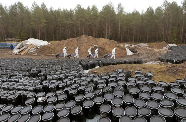 Belarussian rescuers walk at a used pesticides burial site in a forest near the village of Savichi, some 160 km (99 miles) southwest of Minsk, November 14, 2011. About 950 tons of pesticides, including DDT, were extracted from the ground, loaded in plastic barrels and prepared for transportation for utilization in Germany, according to participants.