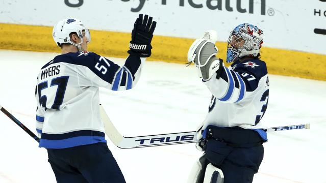Winnipeg Jets goaltender Connor Hellebuyck (37) and defenseman Tyler Myers (57) celebrate at the end of the team's 4-2 win over the Arizona Coyotes in an NHL hockey game Saturday, April 6, 2019, in Glendale, Ariz. (AP Photo/Ross D. Franklin)