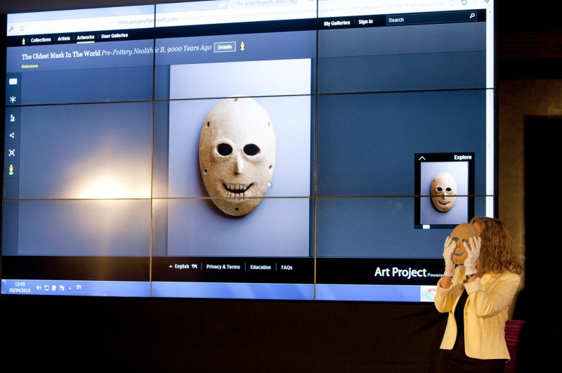 Curator Debby Hershman holds a 9,000 year old Neolithic stone mask, same as the one displayed on a screen during the launch of Google Art project at the Israel Museum in Jerusalem, Tuesday, April 3, 2012. Israel's national museum announced Tuesday it is joining the Google Art project, which provides online tours of museums around the world.(AP Photo/Oded Balilty)